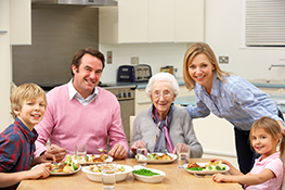 A younger family surrounding an elderly woman at the dinner table