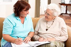A younger woman and older woman sitting together over some paperwork